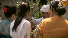 A Hindu family accepts an offering from a priest during a ceremony in Bali Stock Footage