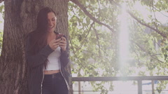 A beautiful girl leaning against a tree and taking selfies with her phone Stock Footage