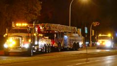 Heavy tow truck pulling away a firetruck at night Stock Footage