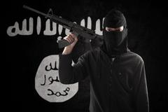 Terrorist with rifle and flag Stock Photos