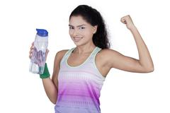 Woman holds water and show her bicep - stock photo