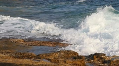 The waves with foam beat against the coast - stock footage