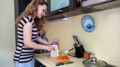 Woman grate orange carrot with shredder tool in kitchen. 4K Stock Footage