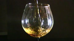 Close up of brandy being poured into snifter against black background - stock footage