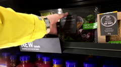 Woman picking salad inside Starbuck store Stock Footage