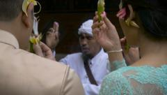 Hand held hindu ceremony in Bali where people hold up flower offerings - stock footage