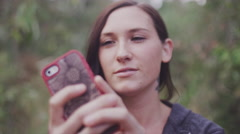 Closeup of a beautiful girl outside using her cell phone, slow motion - stock footage