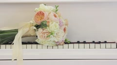 Wedding flowers lie on the keys of the piano. Travel slider - stock footage