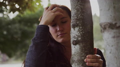 A beautiful girl peeking out from behind a tree, slow motion Stock Footage