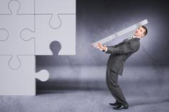 Businessman holding big puzzle piece - stock photo