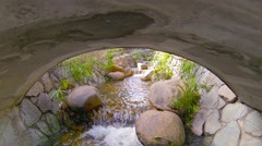 Decorative Stream Flows around Boulders and Under Bridge, with Sound Stock Footage