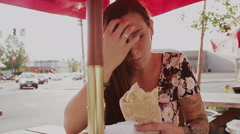 A beautiful girl at an outdoor table eating a burrito Stock Footage
