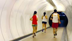 Joggers Running through a Brightly Lit Pedestrian Tunnel Stock Footage