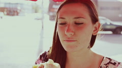 A beautiful girl at an outdoor table eating a burrito and laughing Stock Footage