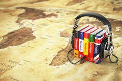 Learning languages online. Audiobooks concept. Books and headphones on the ma - stock illustration