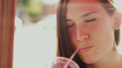 Closeup of beautiful girl at an outdoor table drinking a beverage Stock Footage