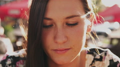 Close up of a beautiful girl sitting at a table in beautiful light smiling Stock Footage