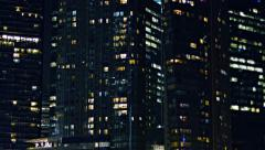 Closeup of backlit windows on contemporary, urban towers at night - stock footage