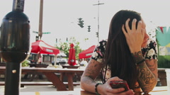 A beautiful girl waiting at an outdoor table and using her phone Stock Footage