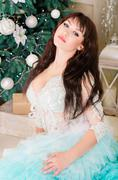 The girl in a wedding dress lace, mint color, sits near a Christmas tree. Stock Photos