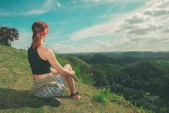 Young woman sitting on a hill and admiring view - stock photo