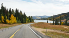 POV-Curving two-lane mountain road beautiful fall colors nearing mountain lake Stock Footage