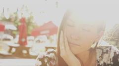 Close up of a beautiful girl sitting at an outdoor table in beautiful light Stock Footage