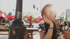 A beautiful girl sitting at a table in beautiful light with lens flare - stock footage