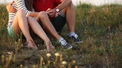Young couple sitting together at the sunset Stock Footage