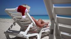 Woman in Santa Claus Hat sitting on sunbed near  tropical calm beach - stock footage