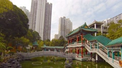 Highrise Buildings Overshadow Buddhist Temple Garden in Southeast Asia Stock Footage