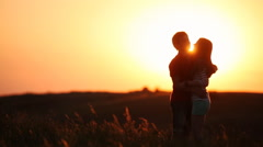 Young couple kissing on the background of a sunset in the field Stock Footage