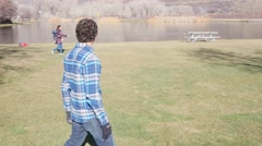 Friends play a game of frisby in the park Stock Footage
