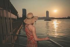 Young woman admiring the sunset over river in city - stock photo
