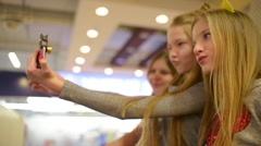 Three young girls make selfie photo with phone in the mall Stock Footage
