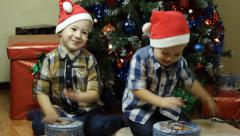 Toddlers playing drums with candy boxes on Christmas - stock footage