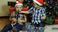 A toddler feeding an other boy with candy on hristmas Stock Footage