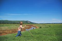 Boy with stick walking Stock Photos