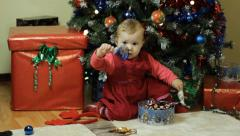 Toddler with handbell next ot a Christmas tree Stock Footage