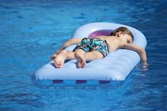 Boy lying on a lilo in a swimming pool - stock photo