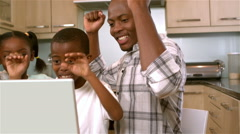 Happy black family rejoicing and using laptop Stock Footage