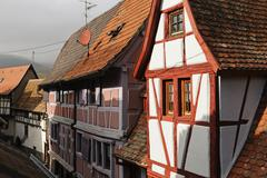 Half-timbered houses on a narrow street in Eguisheim, Alsace, France Stock Photos
