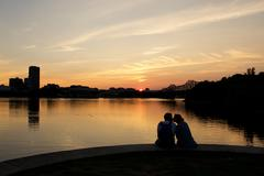 Silhouette of couple sitting by a river kissing, Ottawa, Ontario, Canada Kuvituskuvat