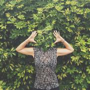 Women with face hidden behind leaves standing with raised arms Stock Photos