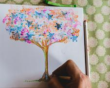 Man drawing an illustration of a magical tree - stock photo