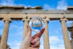 Human hand holding a crystal ball with a reflection of the acropolis, Athens Stock Photos