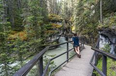 Stock Photo of Girl standing on walkway in Johnston Canyon, Banff National Park, Canadian
