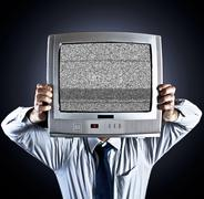 Man holding old fashioned television in front of his face - stock photo