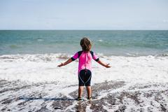 Rear view of a girl in a wetsuit standing in the surf on the beach with her arms Stock Photos