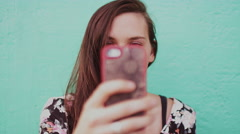 A beautiful girl taking pictures with her cell phone, slow motion Stock Footage